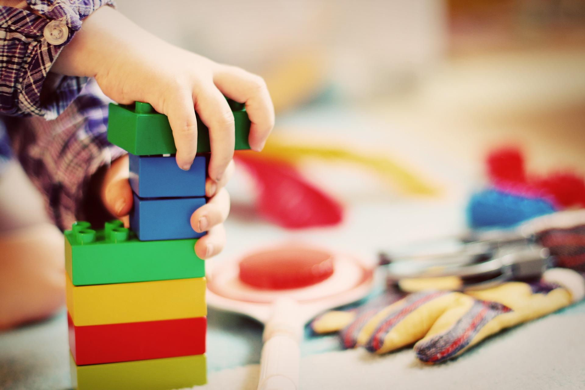 Kinderhände die mit Bauklötzen spielen