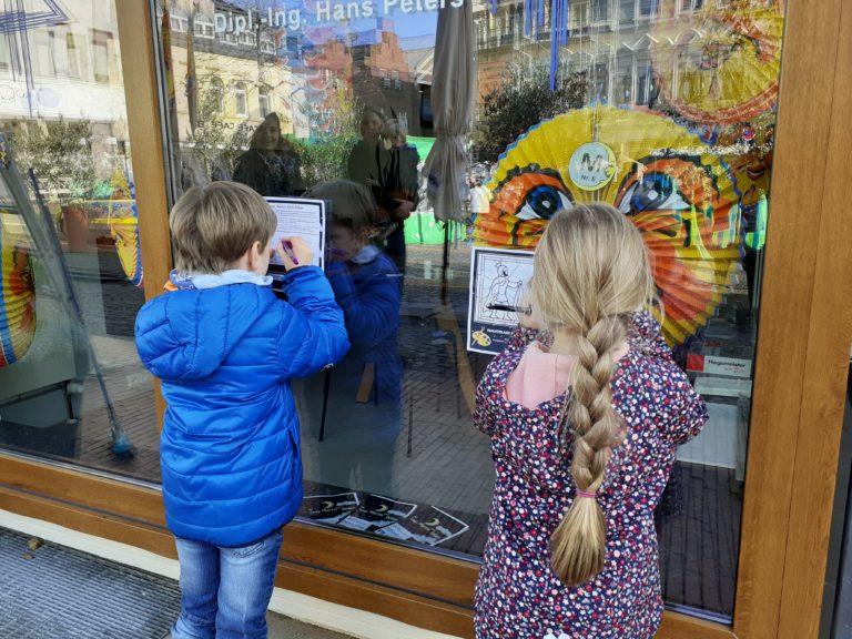 Zwei Kinder stehen an einem geschmückten Schaufenster und füllen das Sankt Martin Gewinnspiel aus.